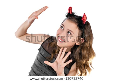A happy teenage girl dressed like a devil in black dress and red horns - stock photo