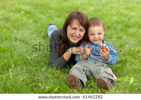 A happy toddler is  sitting on the grass with his mother