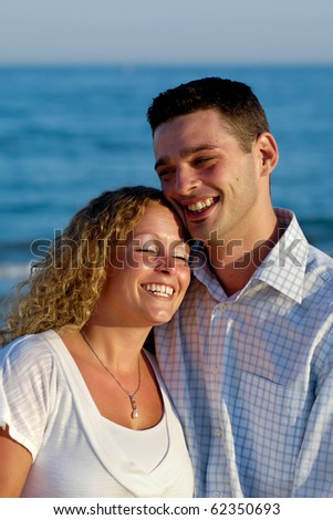 A happy woman and man in love at beach.