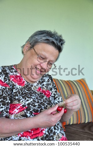 a happy woman holding cherry in order to eat - stock photo