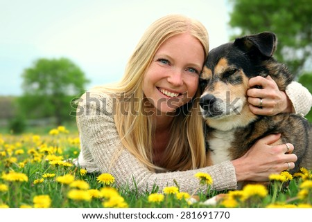 A happy woman is sitting outside in a flower meadow in the country, hugging her German Shepherd Mix breed dog. - stock photo