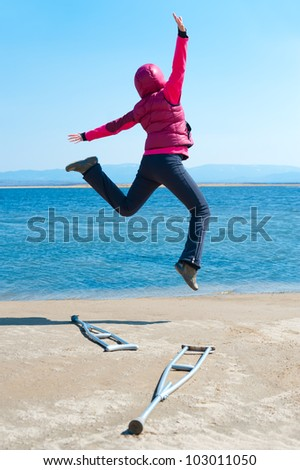 a happy woman jumps, having left her crutches, at a lake shore, back view