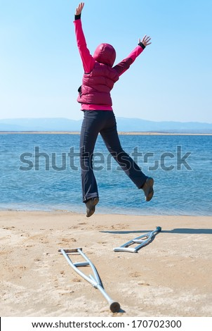 a happy woman jumps, having left her crutches, at a lake shore, back view - stock photo