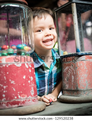 A happy 2 year old asian mixed race boy smiles exuberantly between antique vending machines after winning a small toy from the coin operated dispensers at Bang Nam Pheung floating market in Bangkok - stock photo
