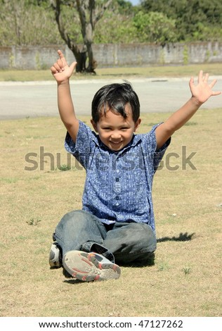 A happy young Asian boy playing outdoor - stock photo