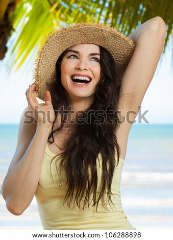 A happy young beautiful woman laughing and holding hat on a tropical beach with palm trees. - stock photo