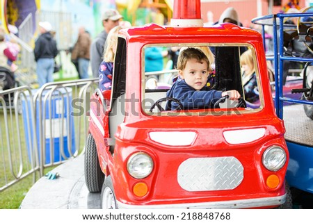 A happy young boy pretending to drive a firetruck on a merry-go-round at a fair or amusement park.  - stock photo