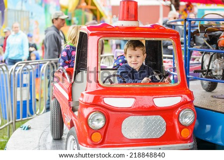 A happy young boy pretending to firetruck on a merry-go-round at a fair amusement park.  - stock photo