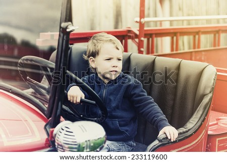 A happy young boy sits in an old shiny vintage red fire truck holding on to the steering wheel looking out.  Processed for a retro, vintage look.