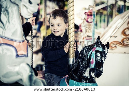 A happy young boy sits on a horse on a merry-go-round carousel ride at a fair or amusement park.  Filtered for a retro vintage look.