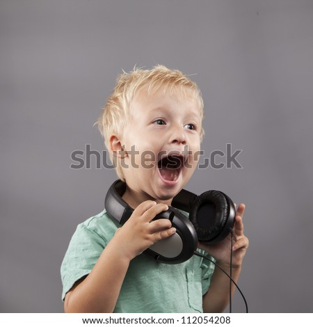A happy young boy with headphones around his neck sings loudly.