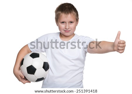 A happy young boy with soccer ball holds his thumb up on the white background - stock photo