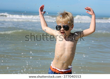 A happy young child is playing in the ocean water on a summer vacation day at the beach.