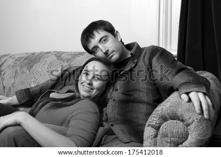 A happy young couple enjoy some cuddling on the couch. - stock photo