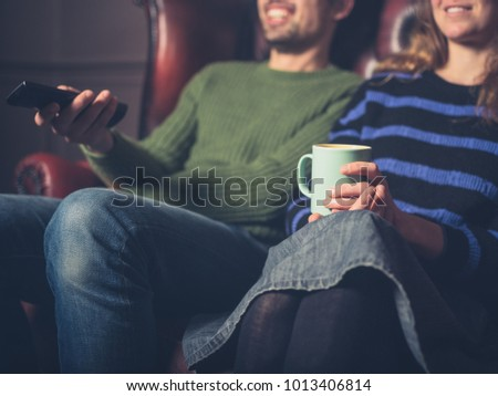 A happy young couple on a sofa are watching television