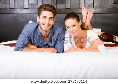 A happy young couple on their vacations lying on the bed in an asian style hotel room.