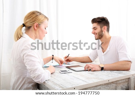 A happy young couple organizing their financial situation at home. - stock photo