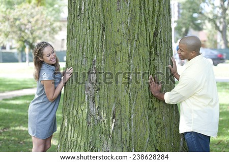 A happy young couple posing on a sunny day next to a large green tree. - stock photo