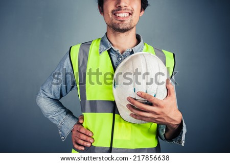 A happy young engineer in high vis vest is holding a hard hat - stock photo