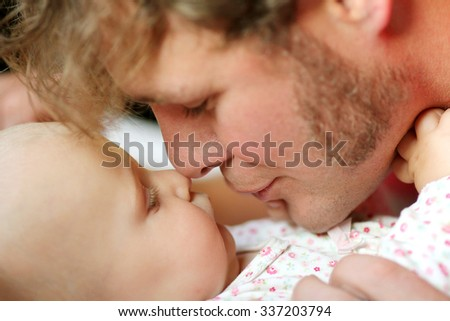 A happy young father is playing with his newborn baby girl, blowing on her nose.