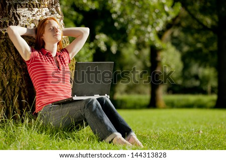 A happy young female student relaxing after doing homework with closed eyes and enjoying the sunshine.
