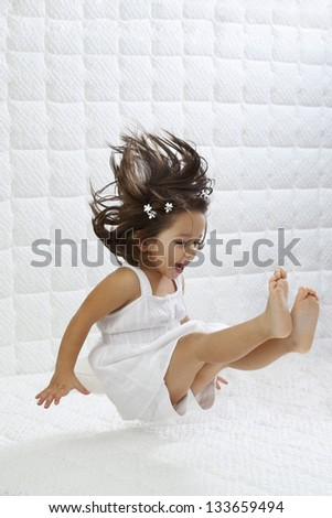 A happy young girl in white dress having fun jumping on bed - stock photo
