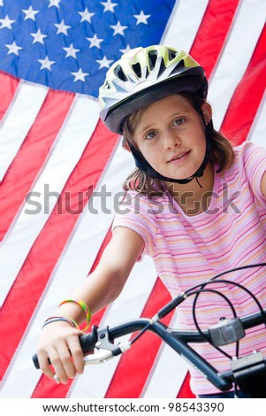 A happy young girl on her bike with an American flag in the background - stock photo
