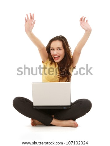 A happy young girl with a laptop sitting on the floor, showing ok, from above - stock photo