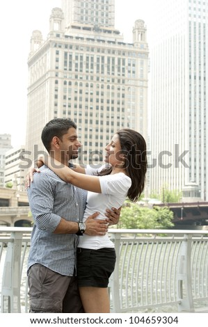A happy young Indian couple with a Chicago Skyline. - stock photo