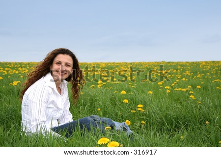A happy young lady in a flowering spring field with a white top
