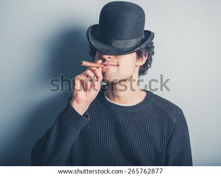 A happy young man wearing a black sweater and a bowler hat is smoking a cigar