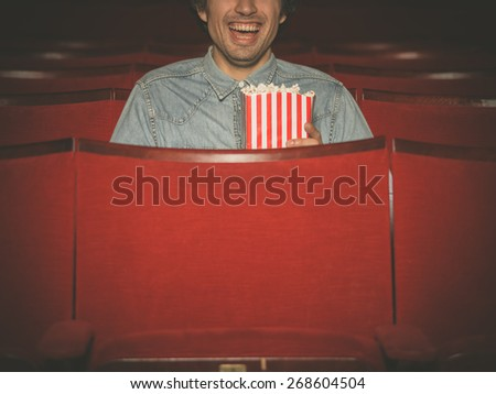 A happy young man with a bucket of popcorn is laughing and watching a movie at the cinema - stock photo