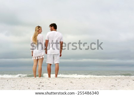 A happy young married couple is holding hands and looking at each other as the stand on a white sand beach looking out over the ocean while on vacation. - stock photo