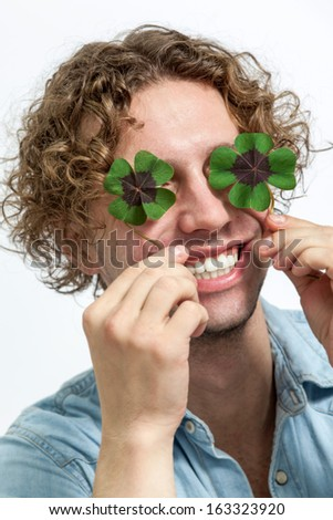 A happy young men covering eyes with fresh 4 leaf clover, isolated on white - stock photo