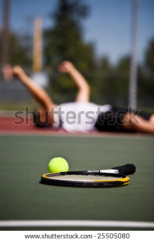 A happy young tennis player lying down on the court after winning