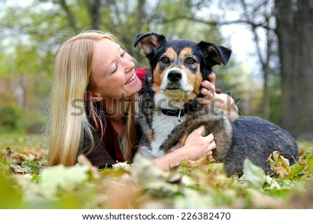 a happy young woman and her German Shepherd dog are laying in the fallen leaves outside hugging on an autumn day. - stock photo