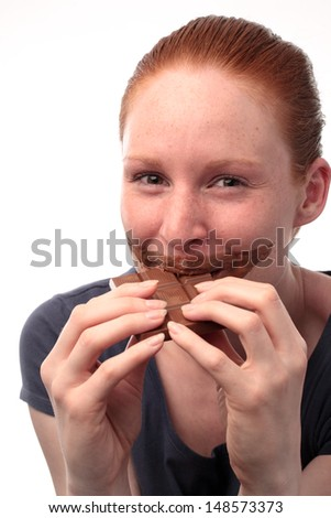 A happy young woman easting a chocolate bar and chocolate marks around her mouth.
