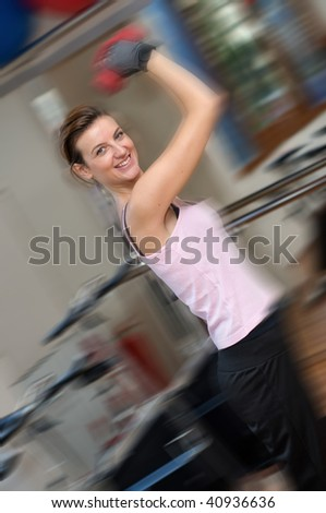 A happy young woman exercising with dumbells standing in front of a glass wall and other exercise equipment. REAR VIEW
