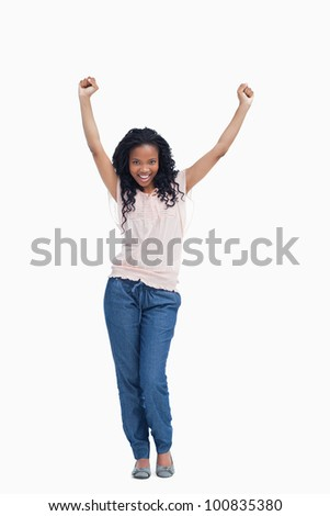 A happy young woman is standing with her hands in the air against a white background