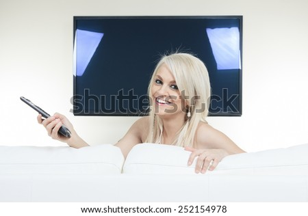 A Happy young woman watching tv on sofa - stock photo