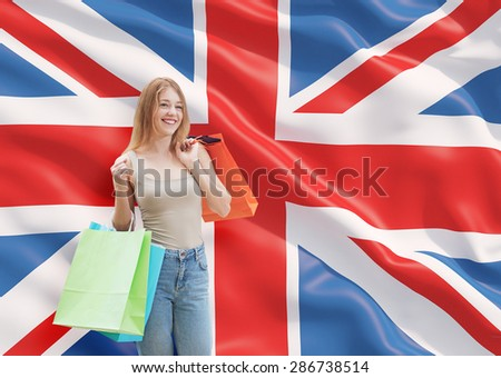 A happy young woman with the colourful shopping bags from the fancy shops. Great Britain flag background. - stock photo