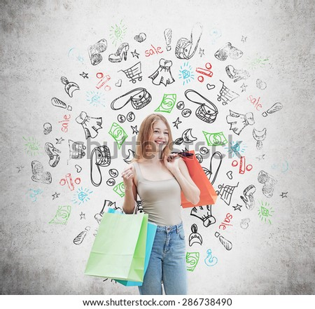 A happy young woman with the colourful shopping bags from the fancy shops. Shopping icons are drawn on the concrete wall. - stock photo