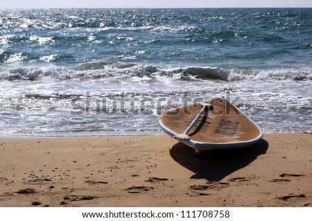 A Hasake lies on a beach. Hasake is a Middle Eastern and Israeli SUP (Stand Up Paddleboard) - surfing sports, usually used by Israeli lifeguards to save swimmers lives from drowning in the sea. - stock photo
