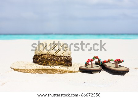A hat and sandals lie on sand - stock photo