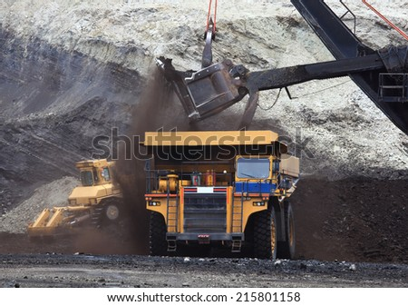 A haul truck is being loaded with dirt and ore at a mine site while another haul truck waits in the foreground. - stock photo