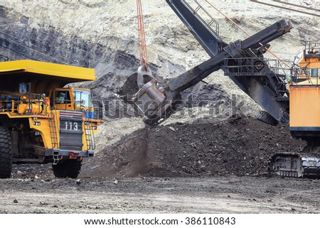 A haul truck is being loaded with dirt and ore at a mine site while another haul truck waits in the foreground.
