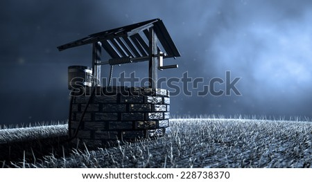 A haunting view of a brick water well with a wooden roof and bucket attached to a rope in a grassy meadow lit by an early evening moon on a dark background - stock photo