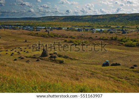 A haymaking in russian village. Beautiful fall landscape.