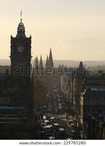 A hazy view along Princes St Edinburgh, from Calton Hill.  The 3 spires in the distance are St Mary's Cathedral.   - stock photo