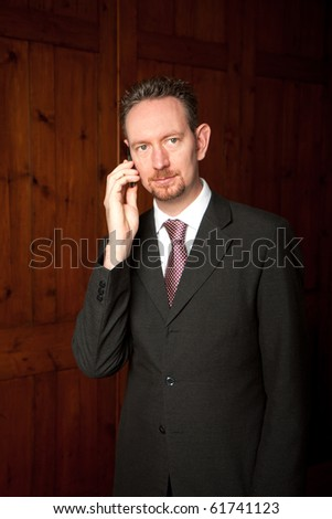 A head and shoulders businessman stood in front of some wooden panels.  He has a phone to his ear and is looking away from the camera. - stock photo